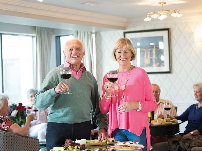 An older man and woman each holding a glass of wine at a Churchill Retirement development