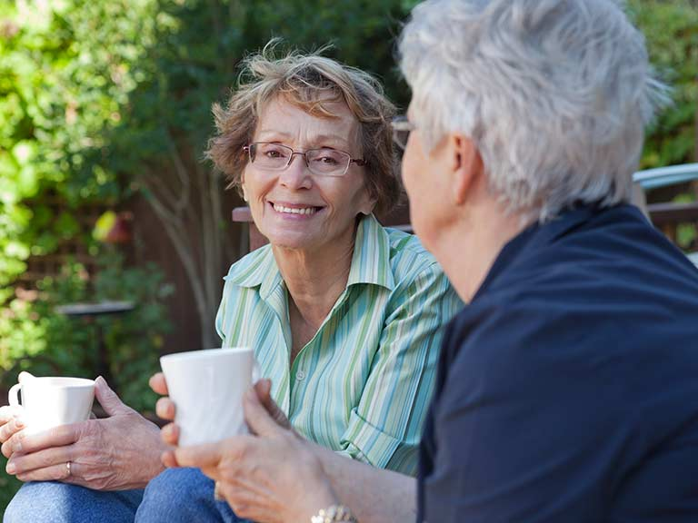 Two older people share a cup of tea - one a volunteer befriender, one a formerly lonely older person