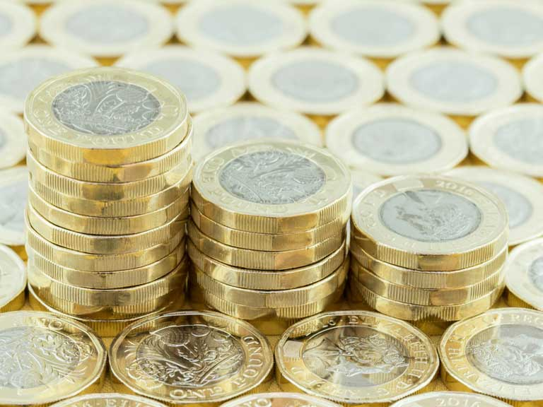 Three stacks of pound coins on a bed of pound coins