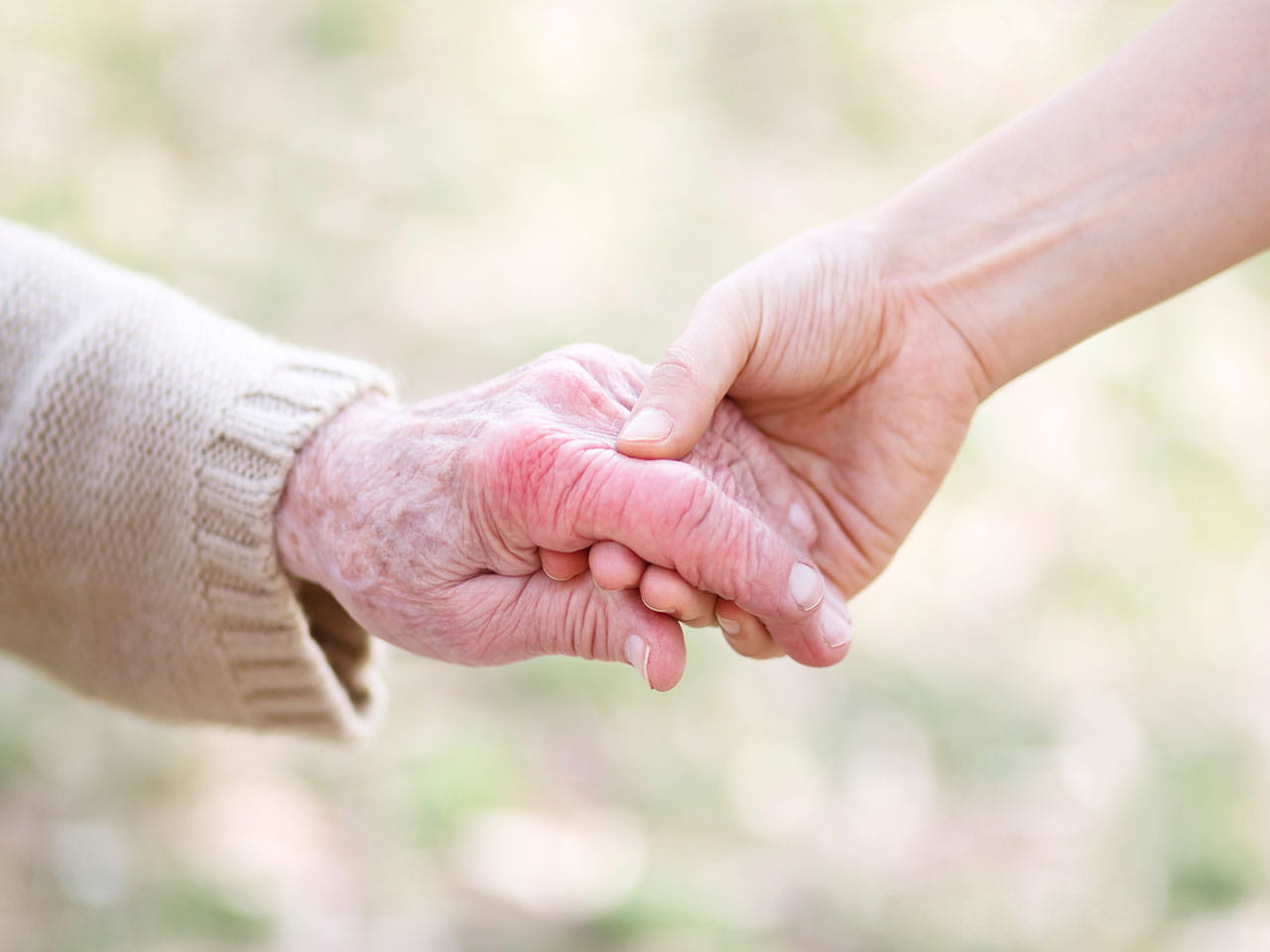 A carer holding their charge's hand to represent someone who needs to know how to claim Carer's Allowance