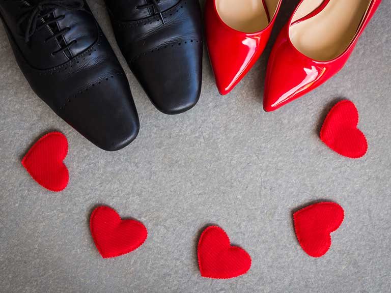 A pair of men's shoes next to a pair of women's shoes and 4 fabric hearts placed beside them on the floor