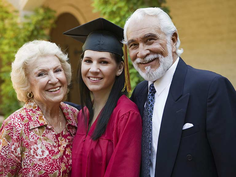A university student stands with her grandparents for a photo at graduation