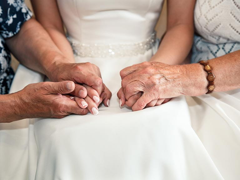 Two grandmothers hold the bride's hands on her wedding day