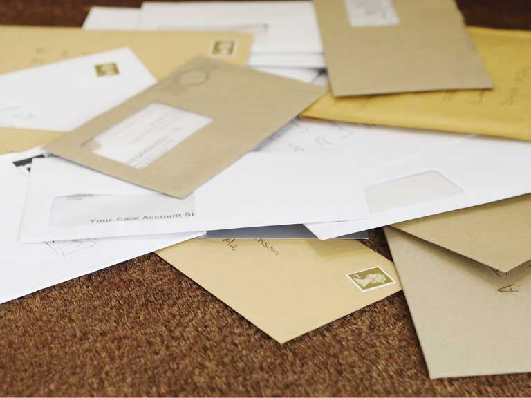 Post piling up on the doormat of an empty house
