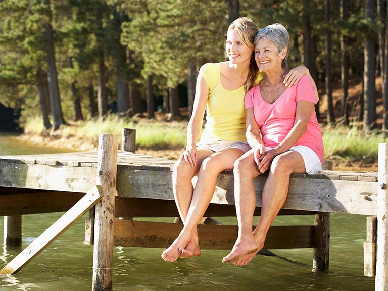 Mature mother and grown up daughter sitting on wooden jetty