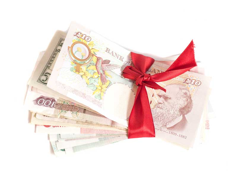 Pile of bank notes wrapped in a ribbon to represent giving money as a gift