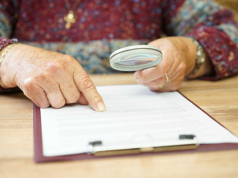 An older woman closely inspecting a will