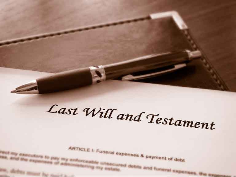 Piece of paper headed Last Will and Testament with a pen resting on the paper