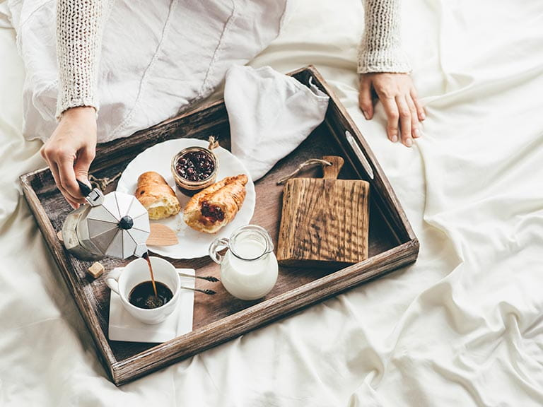 A woman enjoys breakfast in bed at a bed and breakfast