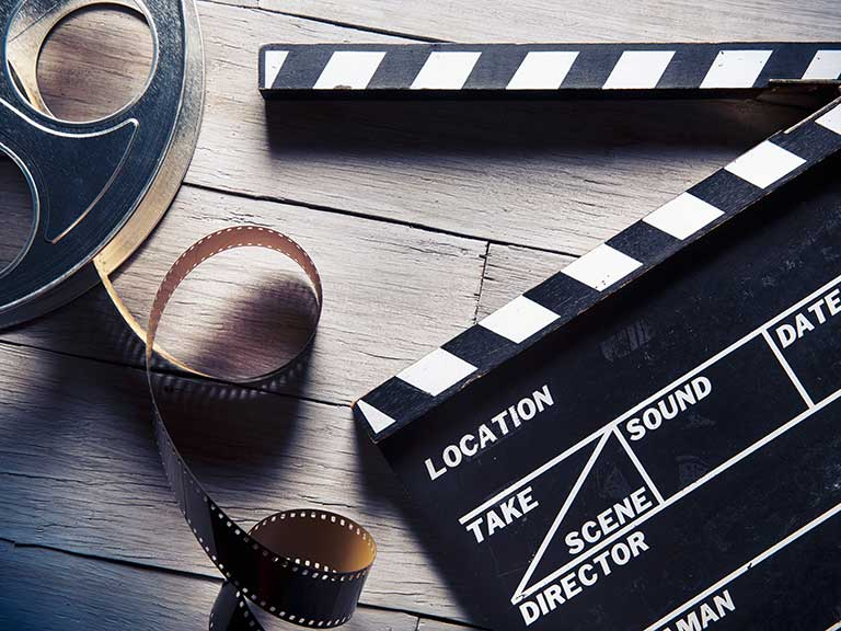 A clapboard and vintage film real to represent working as an extra