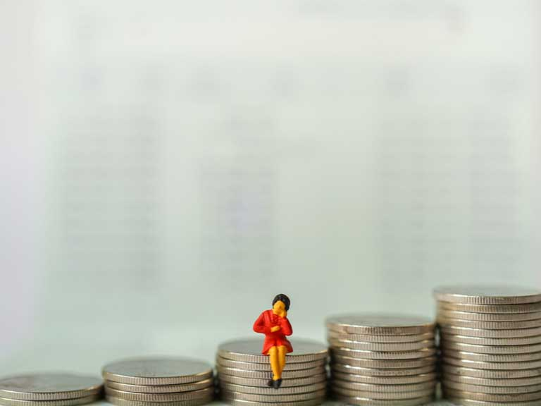 Piles of coins ascending in size with a miniature model of a woman sitting on the middle pile