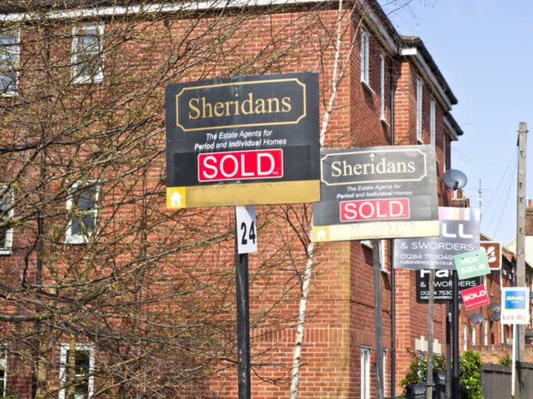 Block of flats with estate agents for sale signs outside