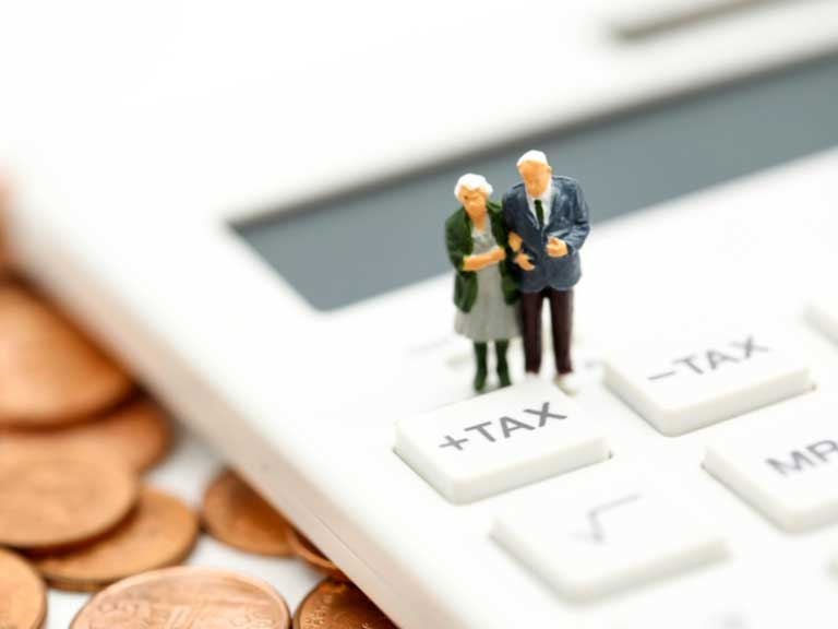 Miniature figures of an older couple standing on a calculator which is resting on coins