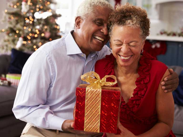 Older couple smiling and laughing as they exchange gifts
