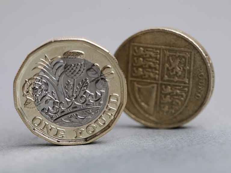 New 12 sided one pound coin in front of an old round one pound coin