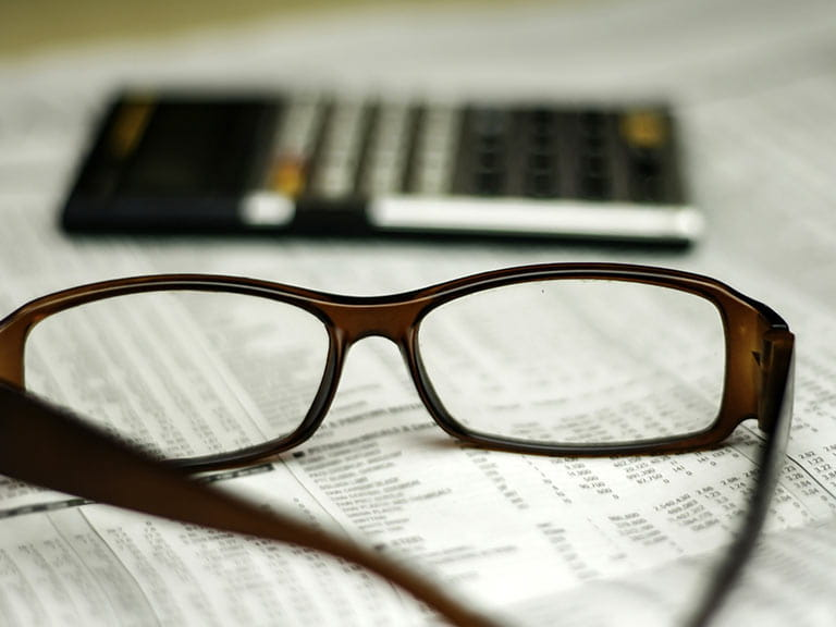 Glasses with calculator and financial paper
