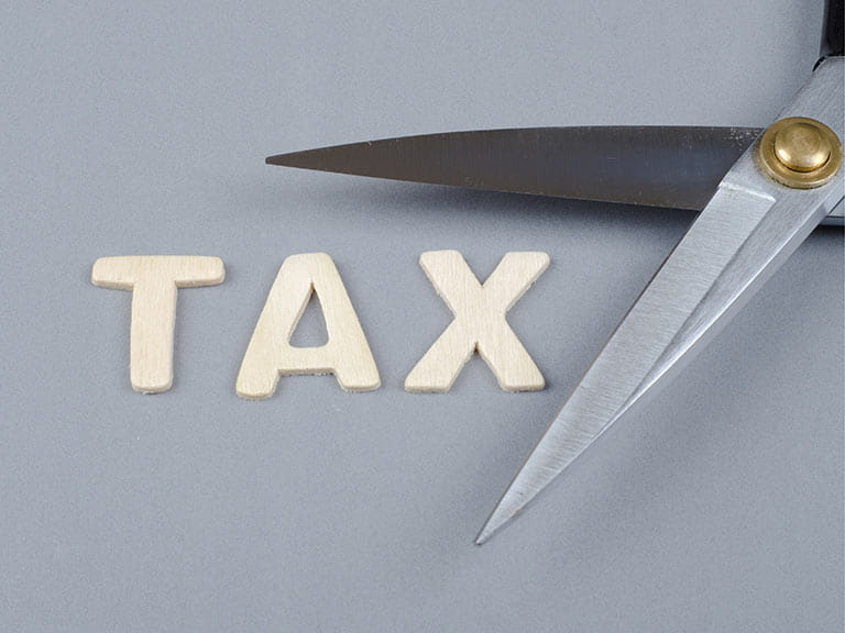 Tax sign being cut by scissors