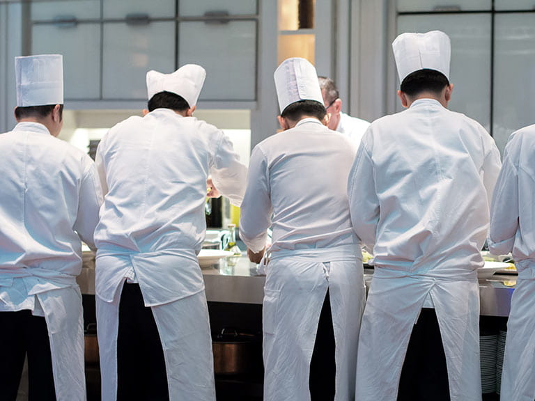 Group of chefs in kitchen plating up