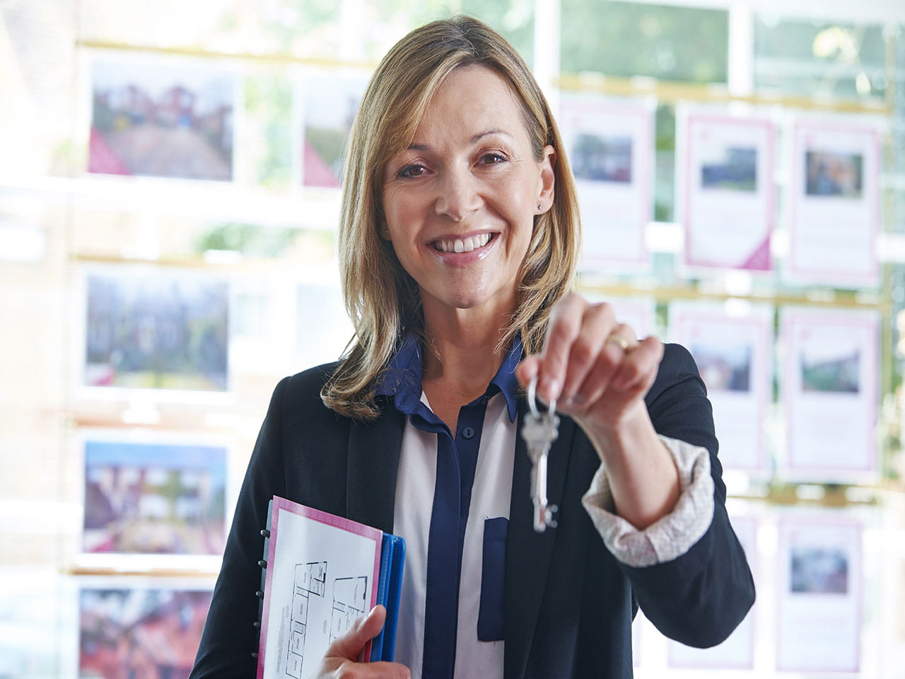 Estate agent holding out keys to a house for sale