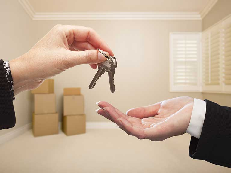 Two people swap keys to represent selling a house