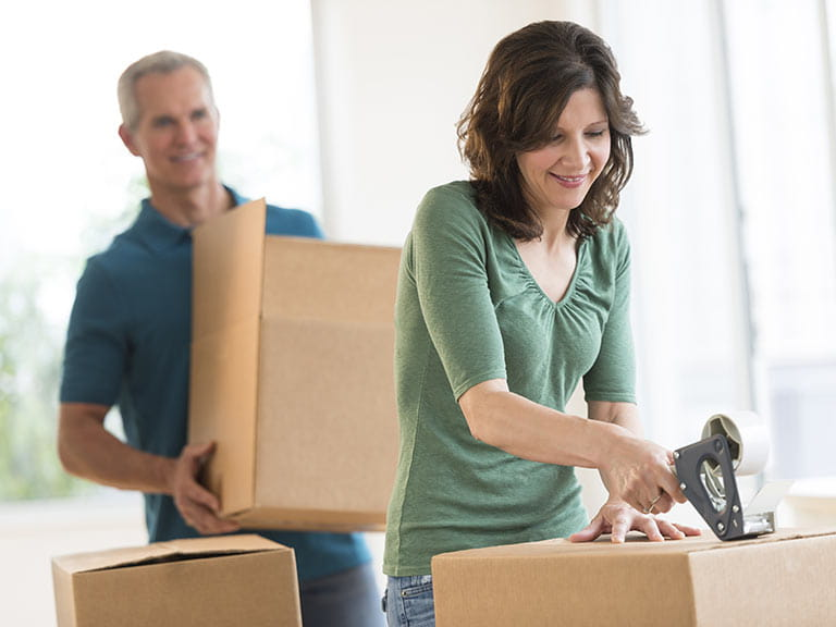 Senior couple packing to move house