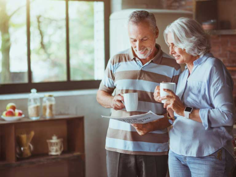 An older couple enjoying a coffee together in their kitchen