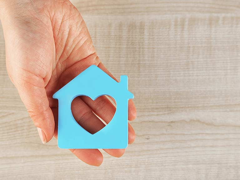 A hand holds a blue cut out of a house with a heart to represent equity release and care home fees
