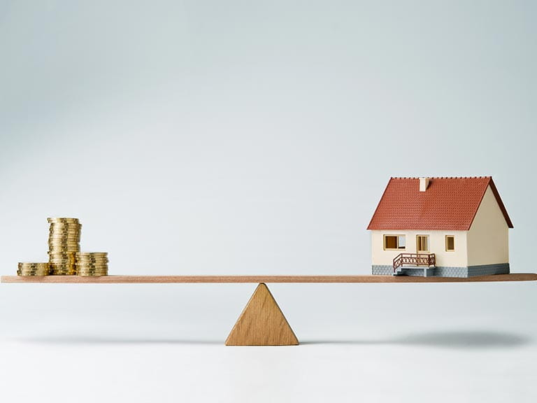 A house balances on a seesaw with money to represent equity release