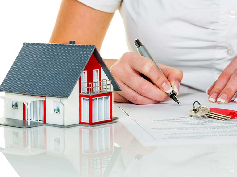 A model of a home stands next to a woman writing on an equity release form