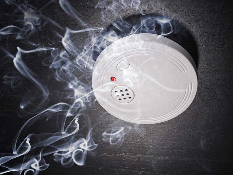 A smoke alarm surrounded by smoke