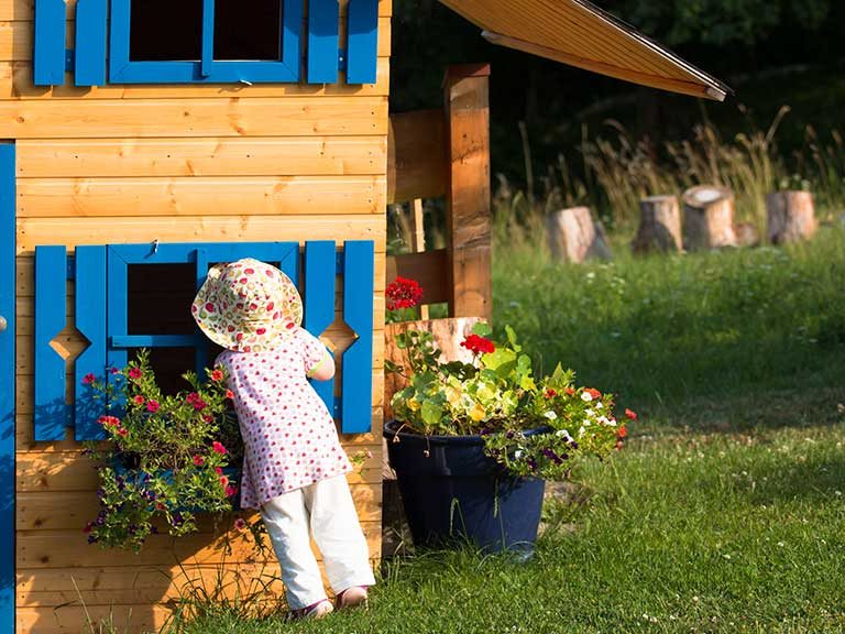 A grandchild peeks through the window of a Wendy house in the back garden