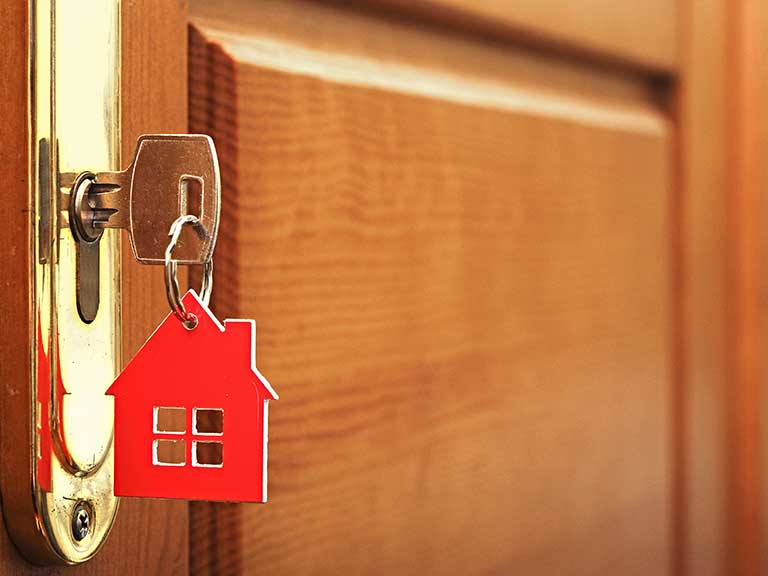 A key in a house door to represent a buy-to-let investment