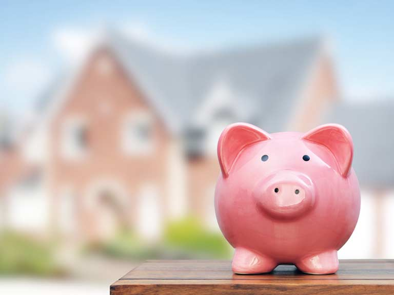 A piggy bank stands outside a home to represent the deposit a renter must pay