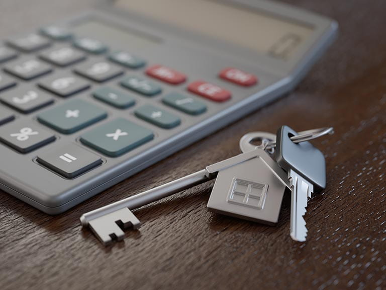 House keys next to a calculator to represent adding up the costs of a buy-to-let mortgage