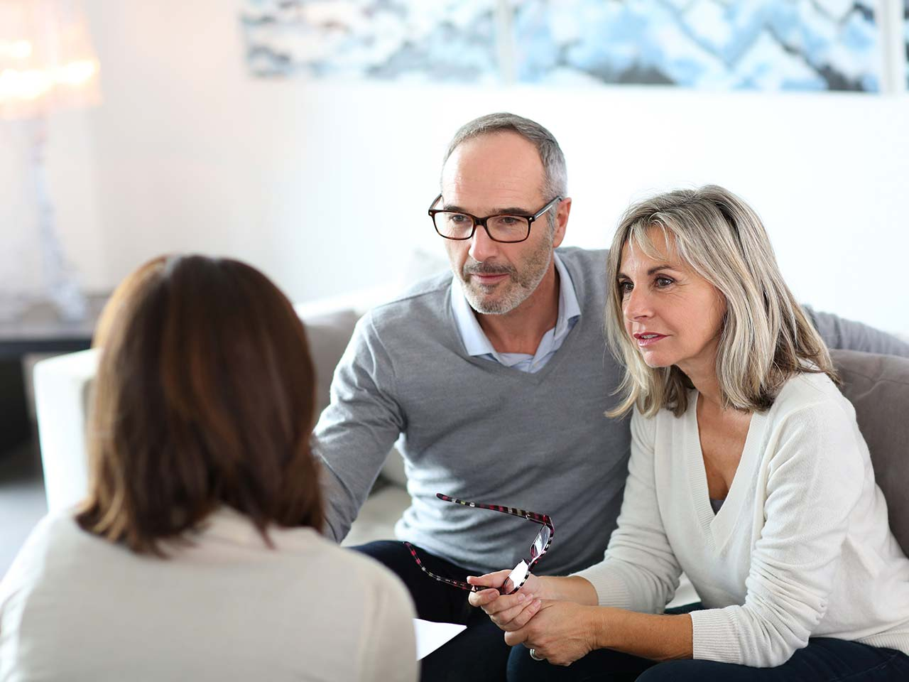 Mature couple talking to mortgage advisor