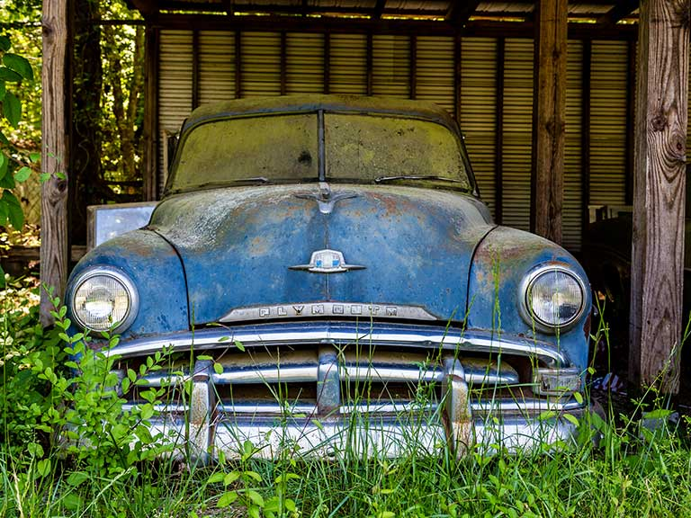 An old car slowly decays in a garden