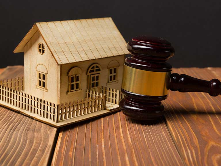 A model of a house and gavel to represent buying a house at auction