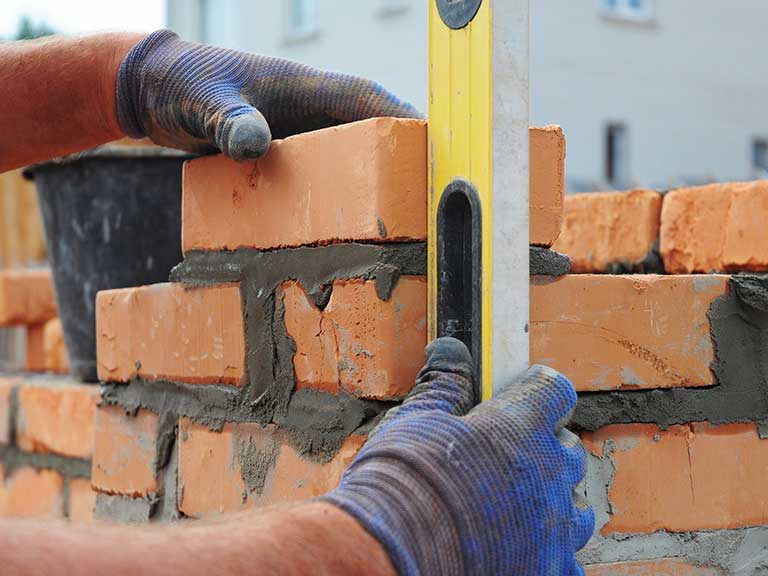A builder builds a brick wall for a house extension