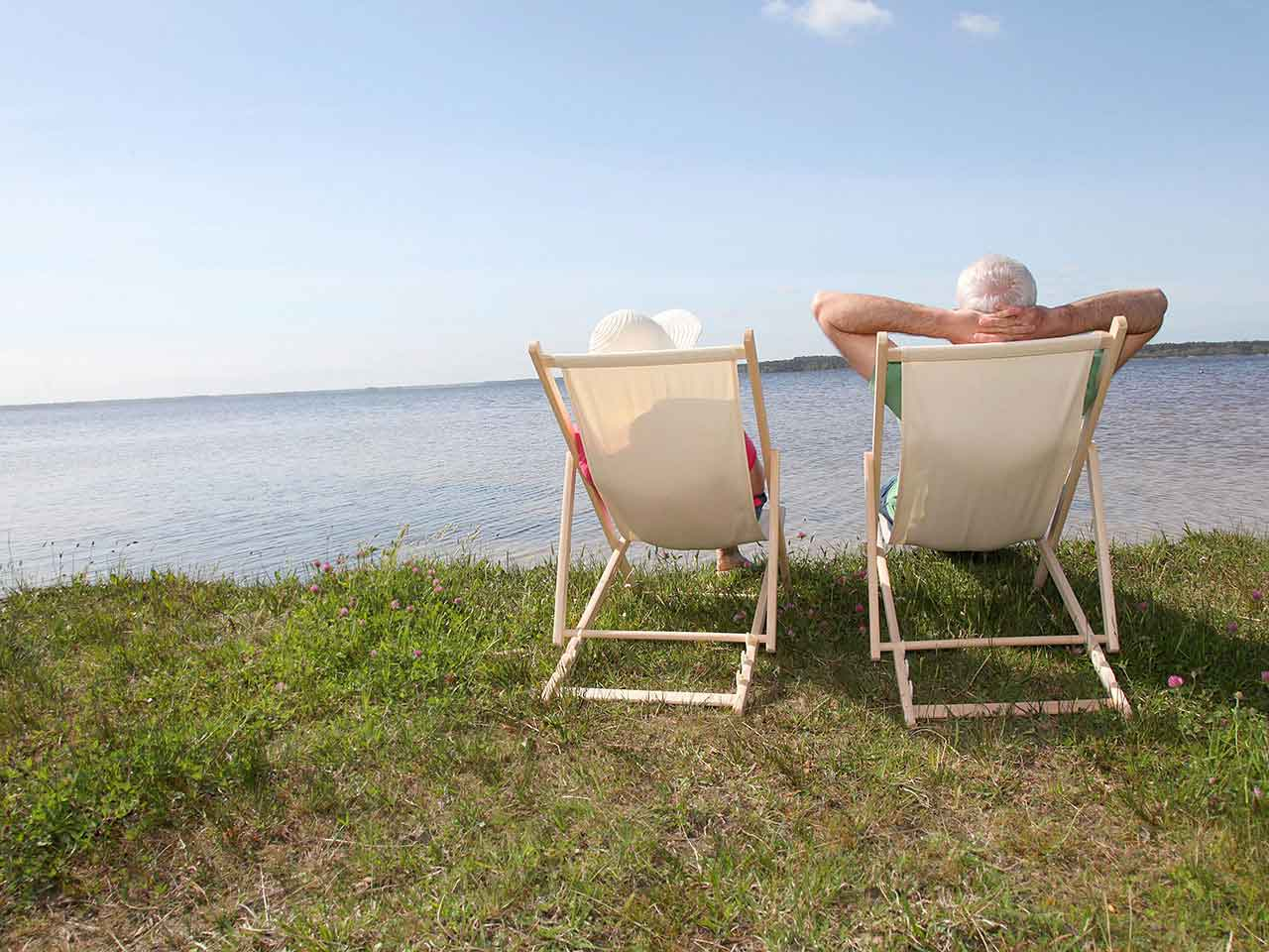 Retired couple sitting on deckchairs on holiday