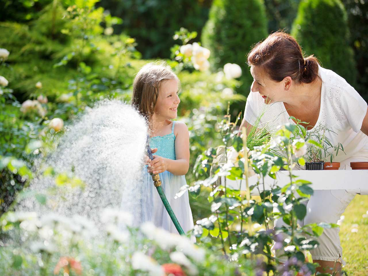 Woman playing in the summer garden with her grandchild