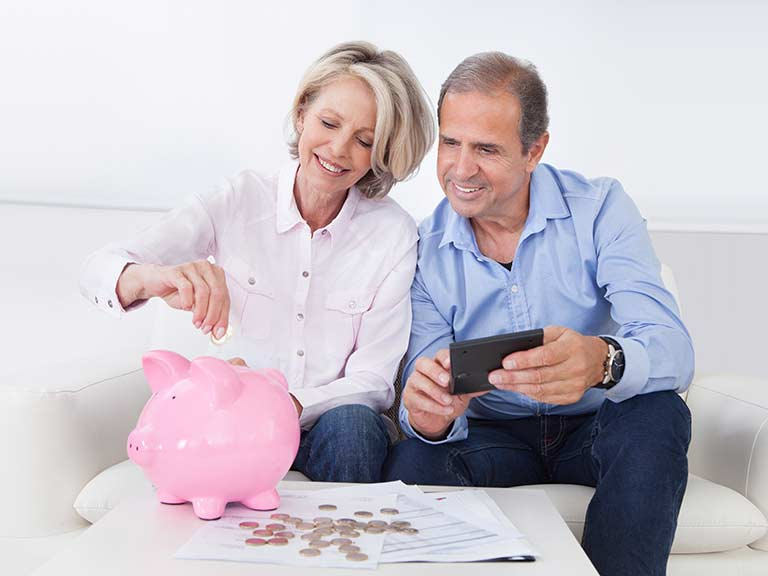 An older couple put coins in a piggy bank to represent the regular income of an annuity