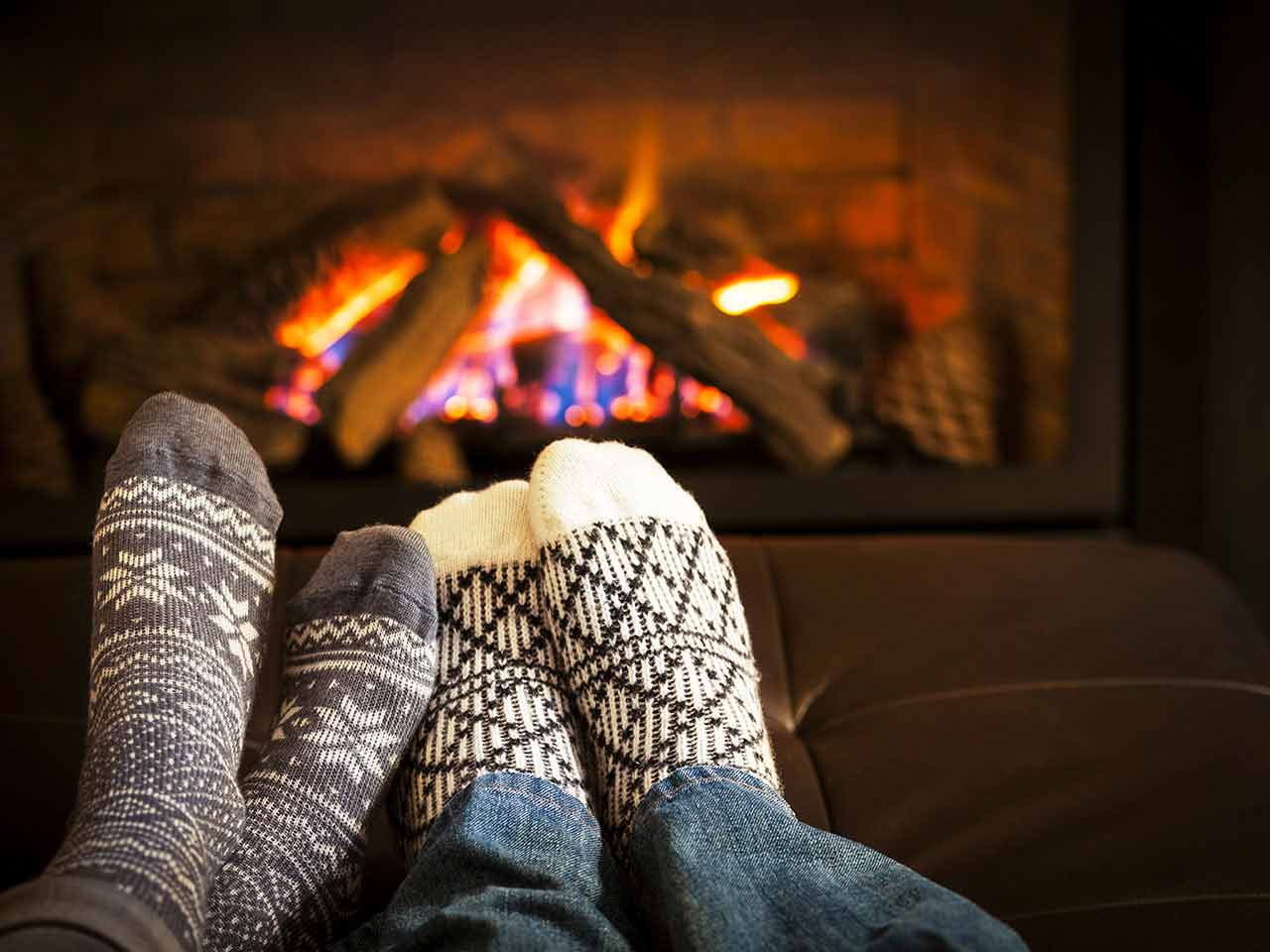 Couple's feet in socks in front of fire to represent the Winter Fuel Payment - a retirement benefit