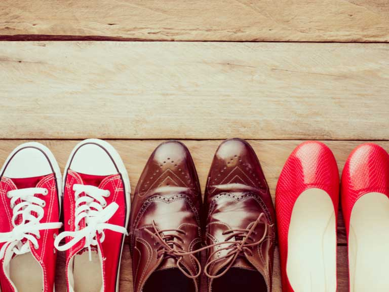 three pairs of shoes in a row - basketball sneakers, traditional brogues and ladies pumps