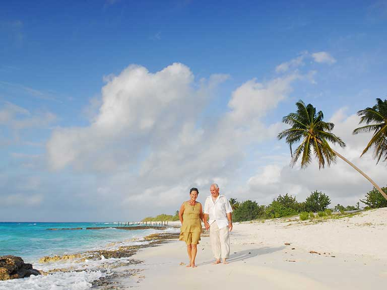 A retired couple stroll on a beach