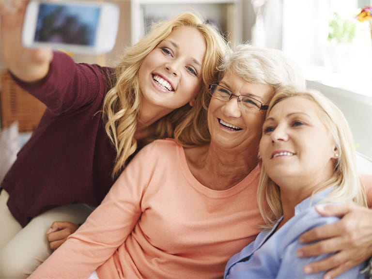 Senior woman taking selfie with daughter and granddaughter