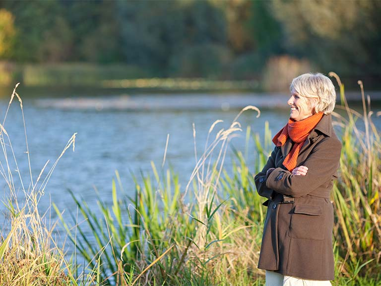 Happy mature woman looking out over a lake
