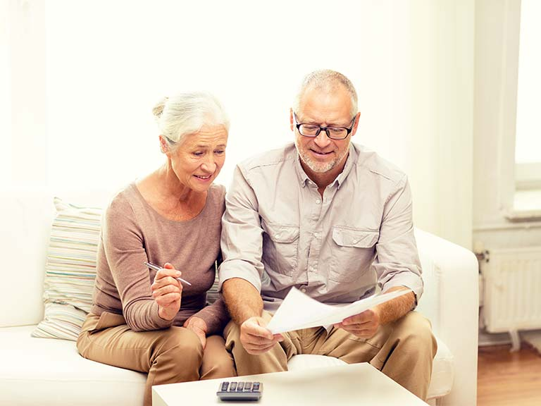 Mature couple with calculator and research