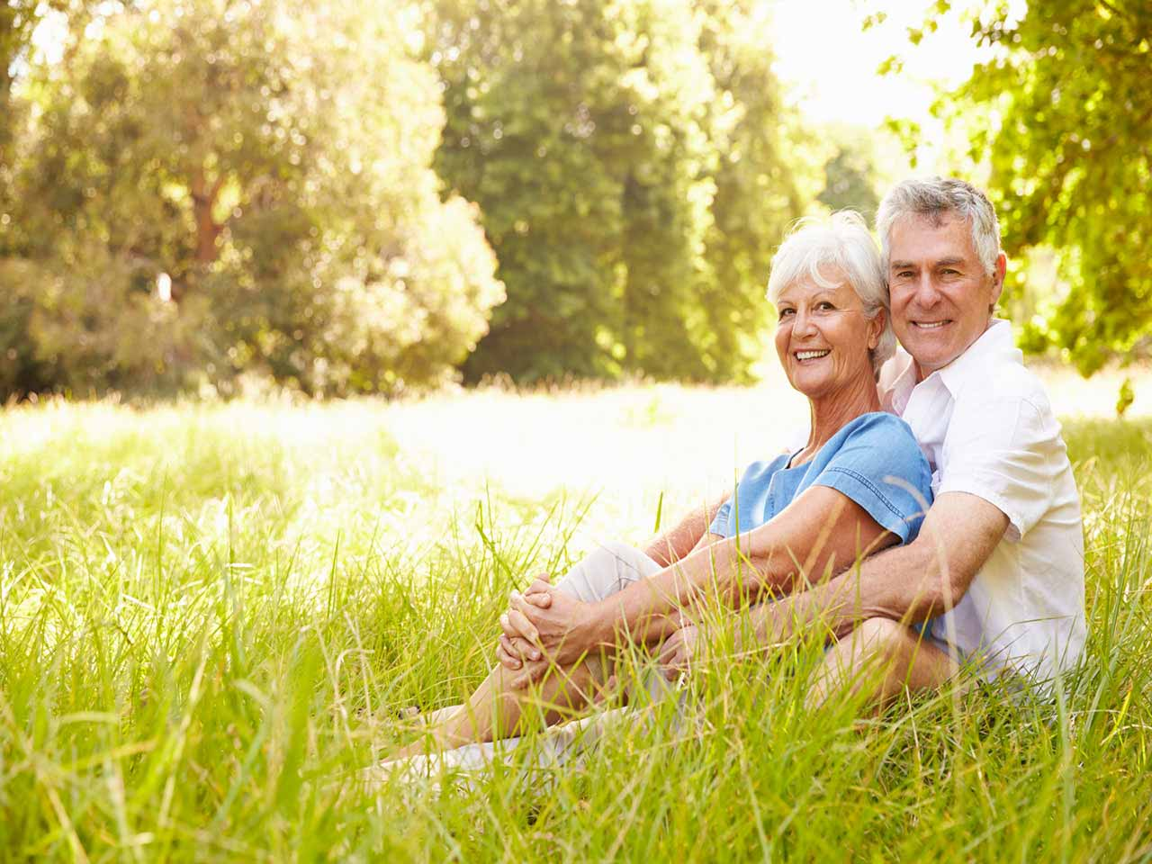 Mature couple sat in field