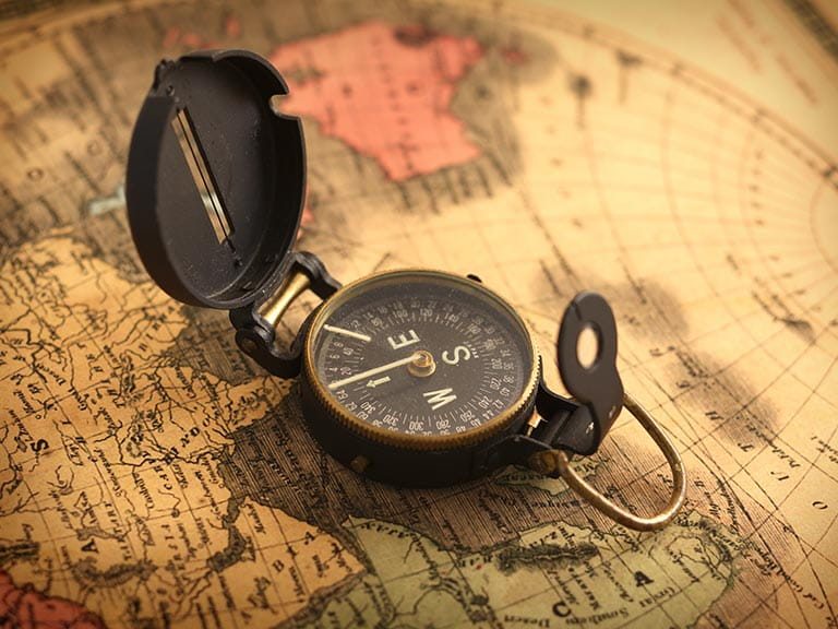 A compass on a globe to represent retiring abroad