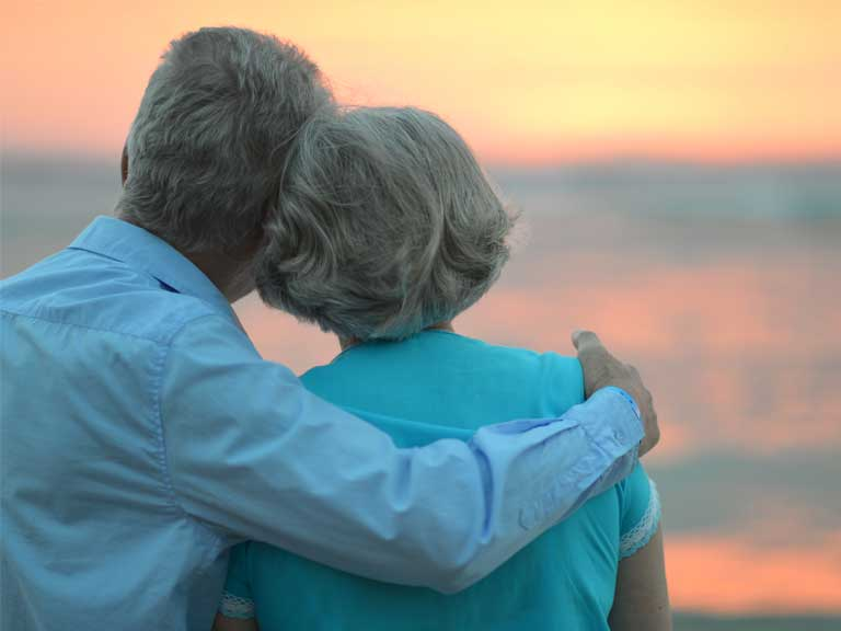 Couple looking into the sunset to represent looking ahead to retirement
